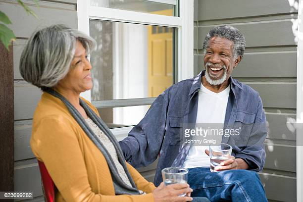 Senior African American couple sitting outside house, laughing