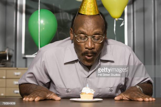 senior african american male worker blowing out birthday candle - blow jobs stock photos and pictures