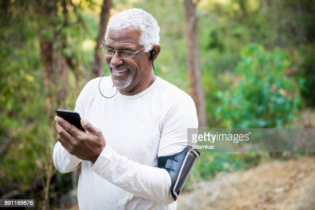 senior african american man checking smartphone - it is finished stock pictures, royalty-free photos & images