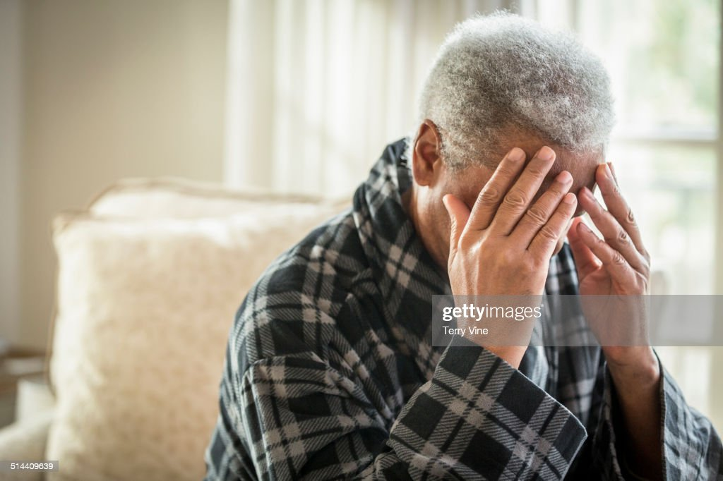 Senior African American man covering his face : Stock Photo