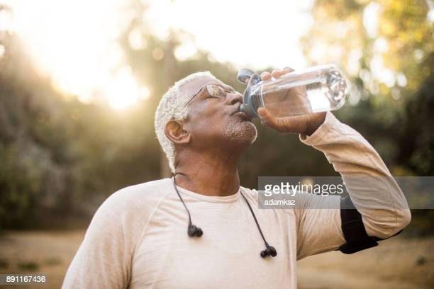senior african american man drinking water - water stock pictures, royalty-free photos & images