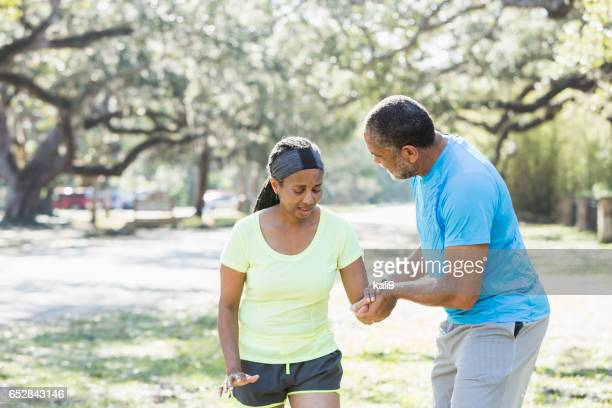 Senior African American man helping woman walk slowly