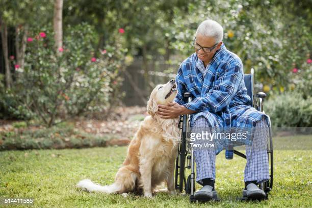 senior african american man in wheelchair petting dog - guide dog photos et images de collection