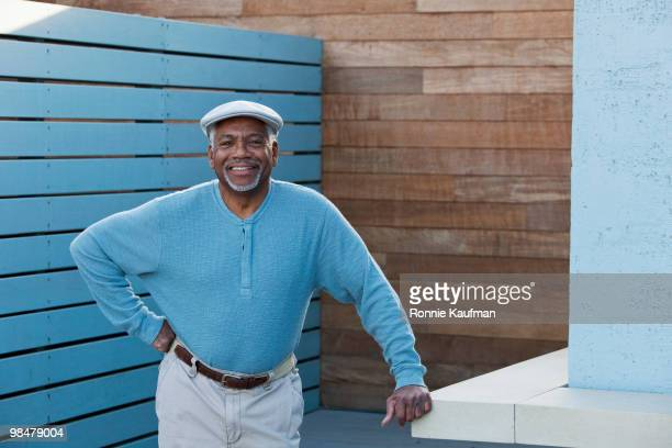 senior african american man leaning on counter - one senior man only stock pictures, royalty-free photos & images