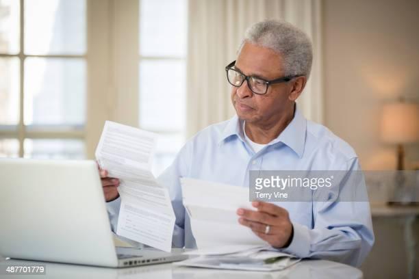 Senior African American man paying bills