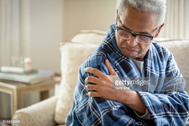 senior african american man rubbing his shoulder - shoulder stock pictures, royalty-free photos & images