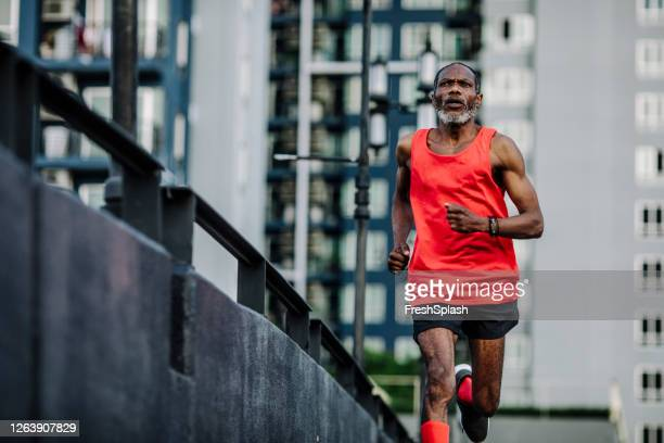 senior african american man running in a city - marathon stock pictures, royalty-free photos & images