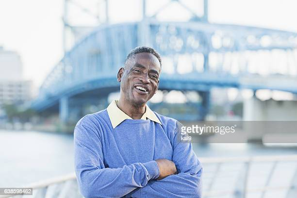 Senior African American man standing on city waterfront