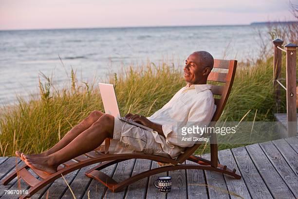 senior african american man typing on laptop - barefoot black men stock pictures, royalty-free photos & images