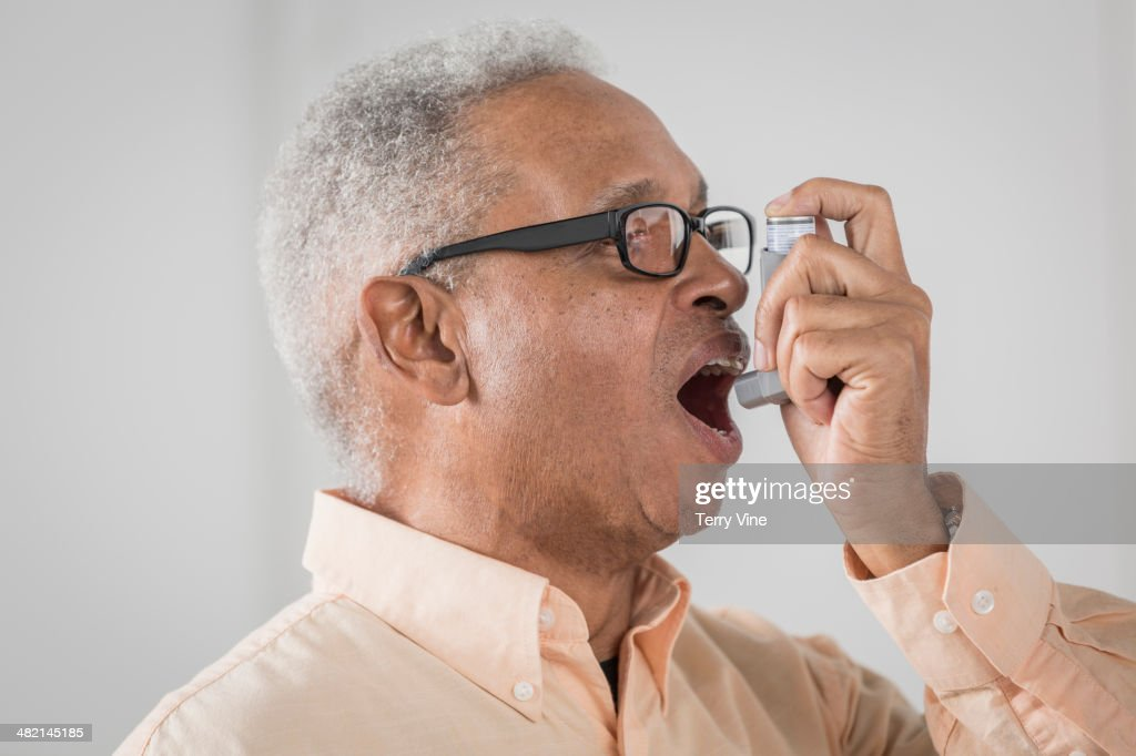 Senior African American man using asthma inhaler : Stock Photo