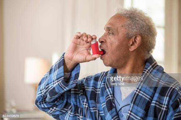 senior african american man using inhaler - bomba para asma imagens e fotografias de stock