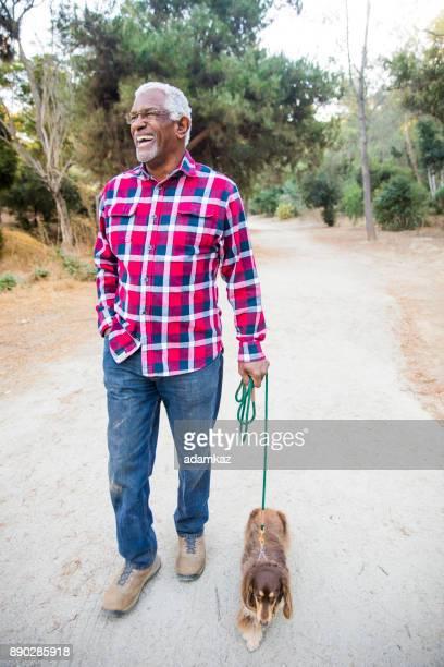 Senior americano africano hombre pasear a su perro