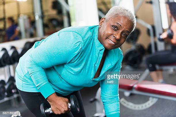 Senior African American woman at gym lifting weights