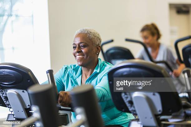 Senior African American woman at gym on exercise bike