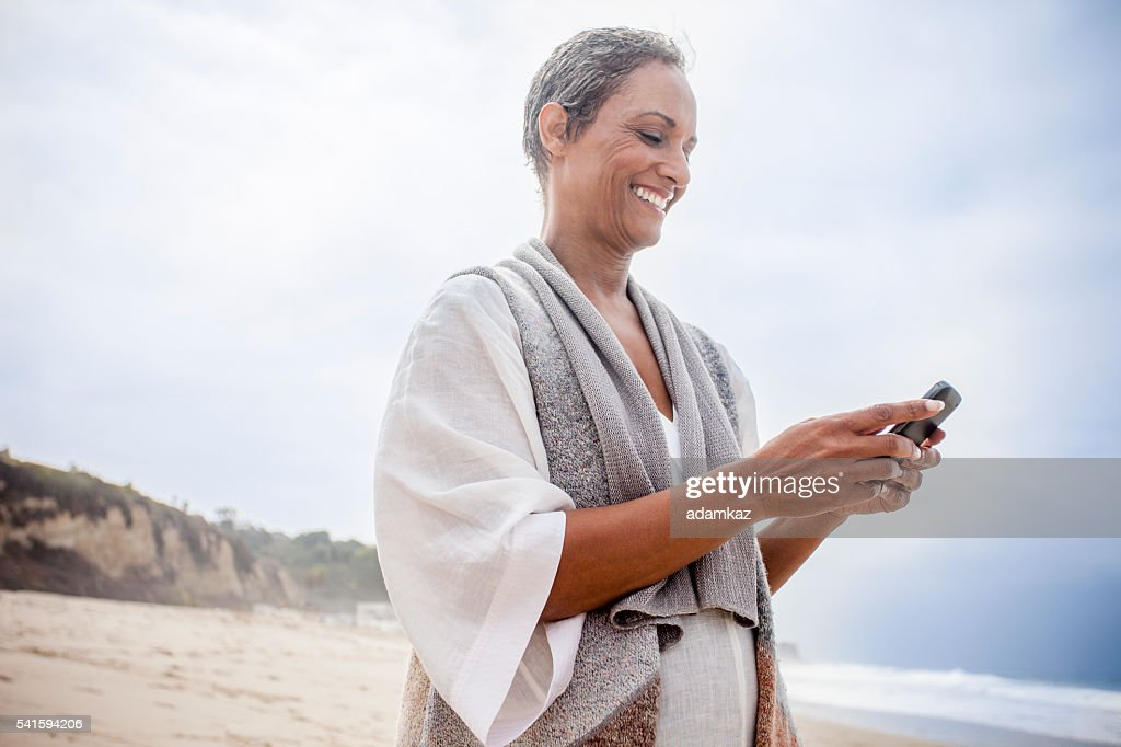 Senior African American Woman Checking Smartphone : Stock Photo