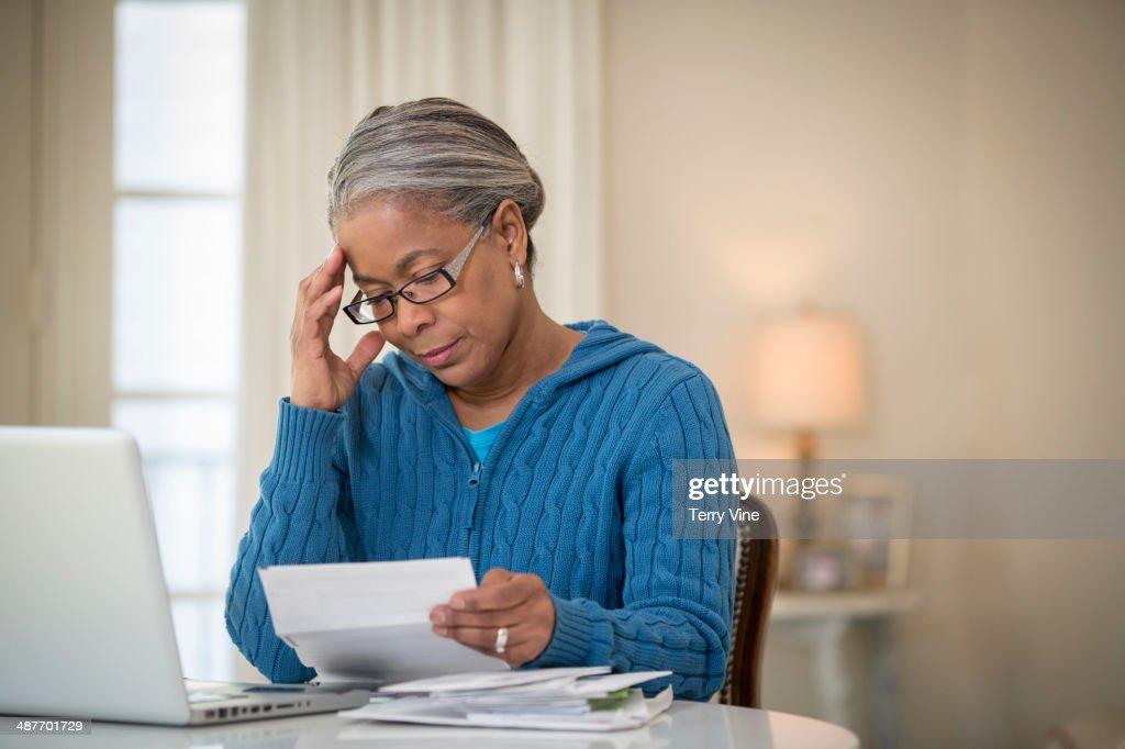 Senior African American woman paying bills : Stock Photo
