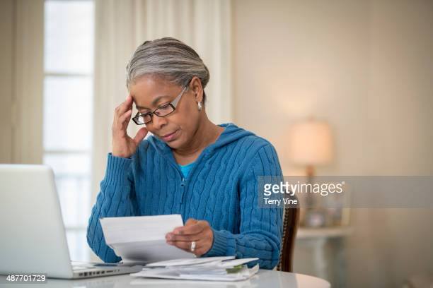 senior african american woman paying bills - bankruptcy stock pictures, royalty-free photos & images