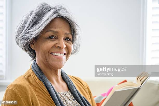 Senior African American woman smiling towards camera with book