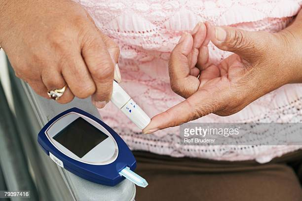 Senior African American woman testing blood sugar