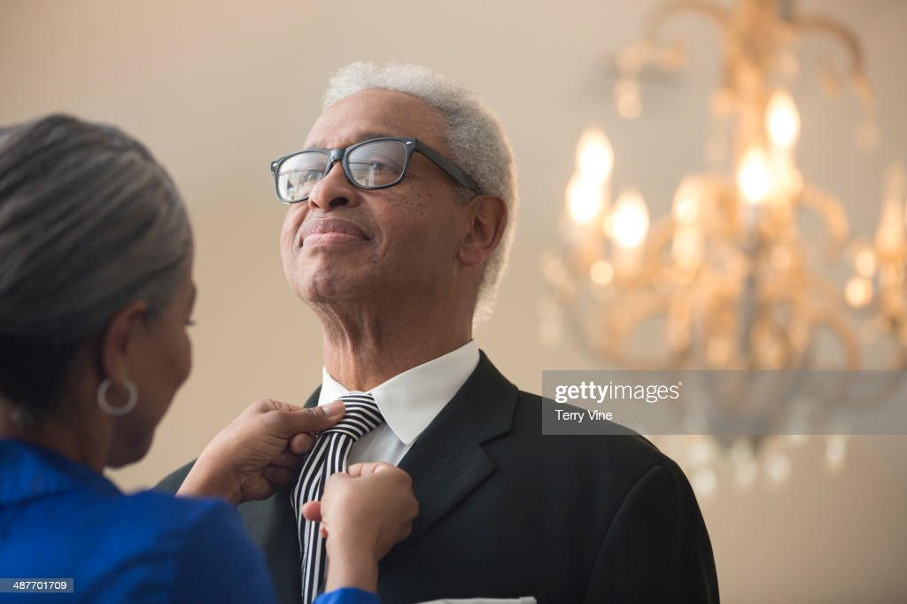 Senior African American woman tying husband's tie : Stock Photo