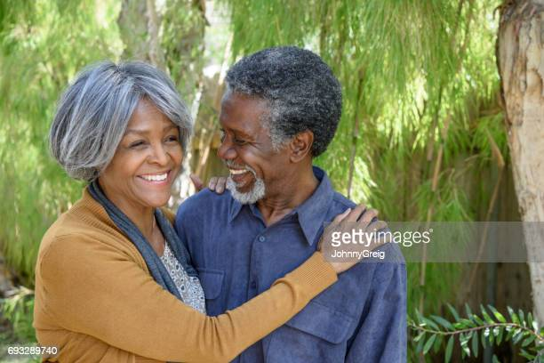 senior african american woman with hand on mans shoulder, smiling - 60 69 years stock pictures, royalty-free photos & images