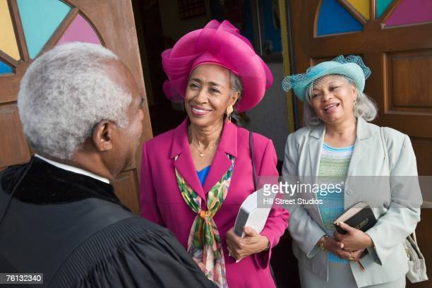 senior african american women talking to reverend - black hat stock pictures, royalty-free photos & images