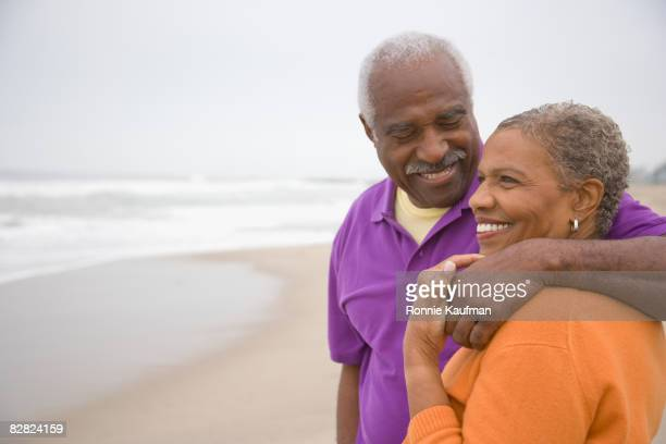 Senior African couple hugging at beach