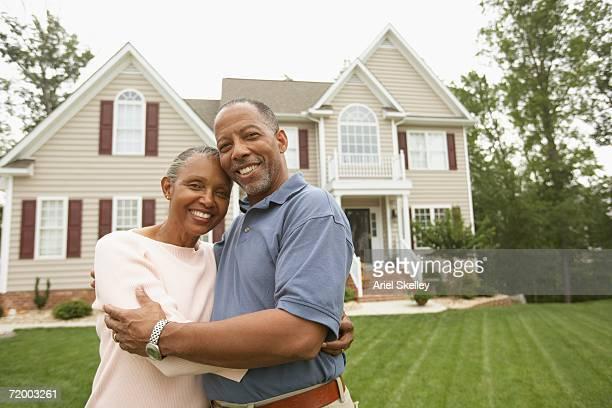 senior african couple hugging in front of house - voor stockfoto's en -beelden
