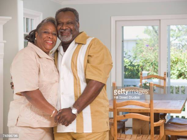 senior african couple hugging indoors - fat black man stock photos and pictures