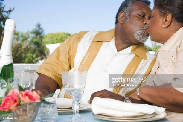 Senior African couple kissing outdoors
