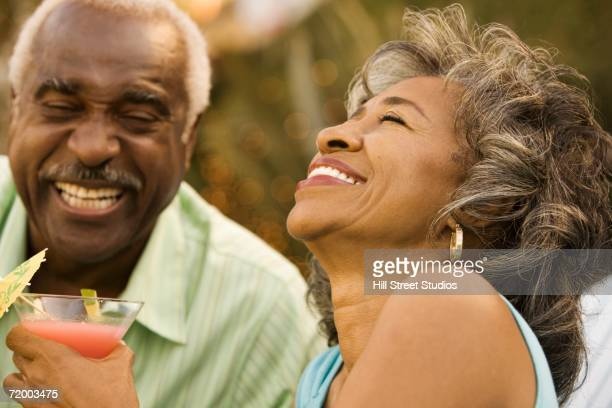 Senior African couple laughing outdoors