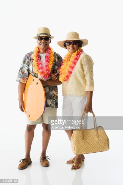 senior african couple on vacation - woman carrying tote bag stock photos and pictures