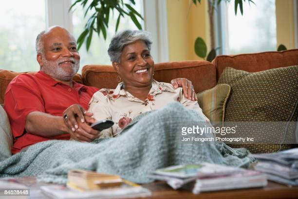 Senior African couple watching television