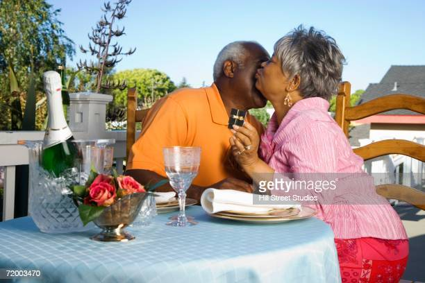 Senior African couple with champagne and gift box kissing outdoors