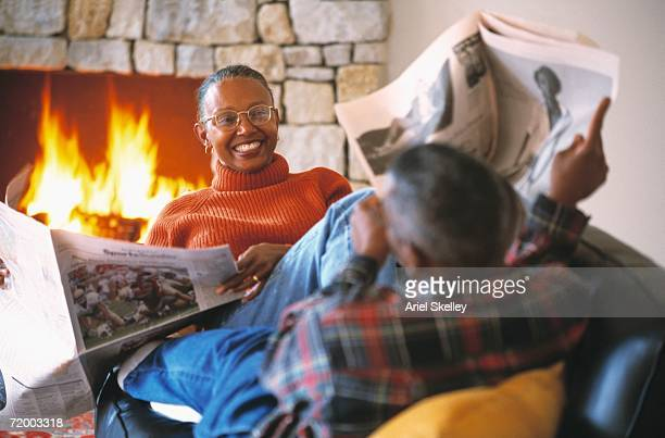 senior african couple with newspapers on sofa - hot older women stock pictures, royalty-free photos & images