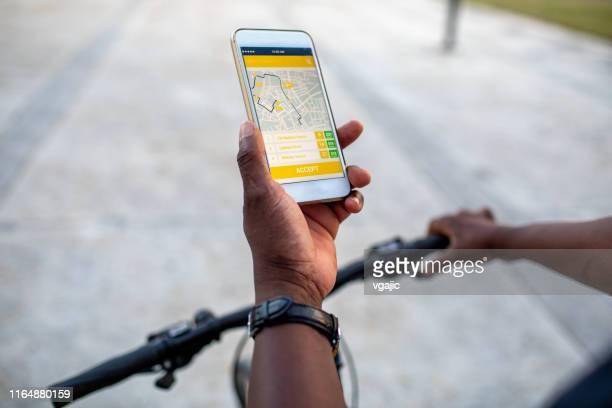Senior African Delivery Man Checking Mobile App For Direction In the City