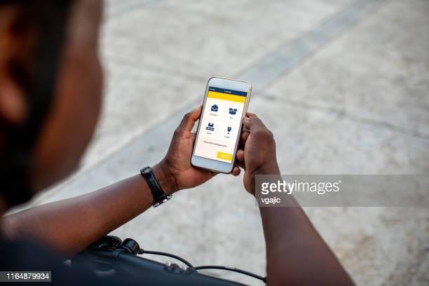 homem de entrega africano sênior que verific o app móvel - carteiro - fotografias e filmes do acervo