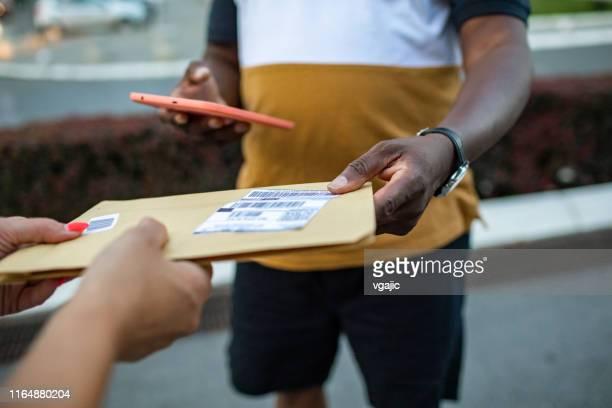 homem de entrega sênior africano entregando o pacote ao cliente - carteiro - fotografias e filmes do acervo