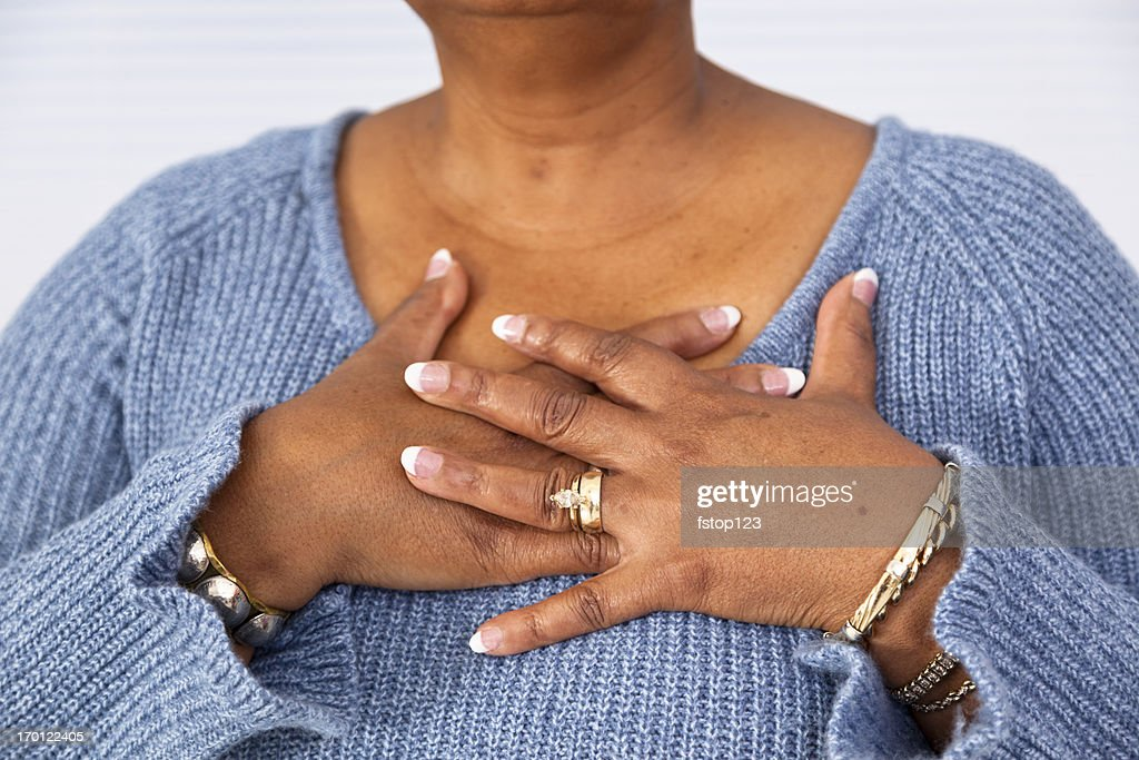 Senior African descent woman clutches chest in pain : Stock Photo