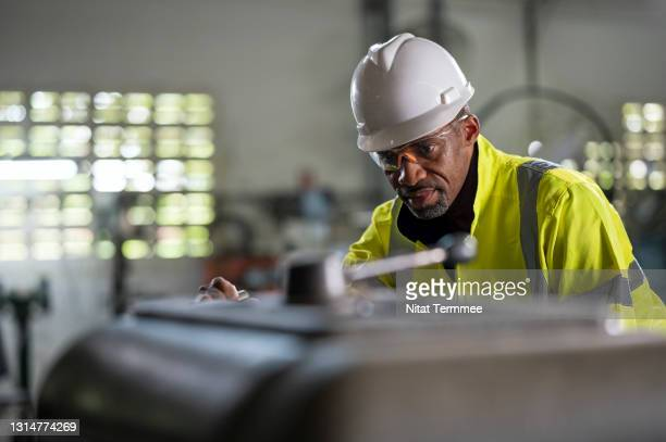 senior african engineer operating on a lathe machine in the engineering part production line. - improvement stock pictures, royalty-free photos & images