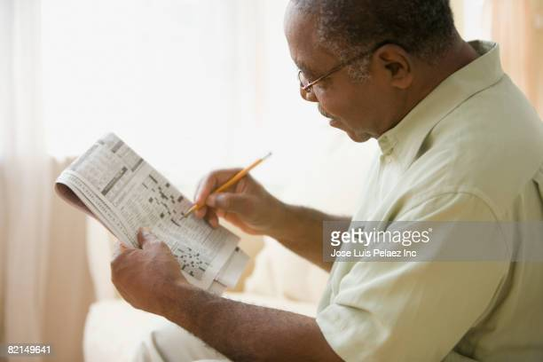 Senior African man doing crossword puzzle