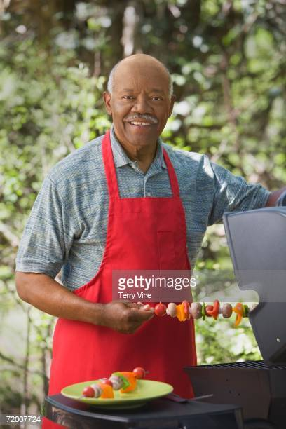 Senior African man grilling outdoors