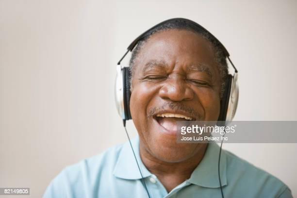 Senior African man listening to headphones