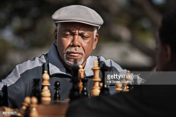 Senior African man playing chess outdoors