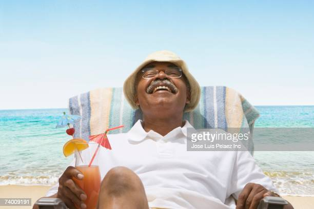 senior african man relaxing in beach chair - outdoor chair stock pictures, royalty-free photos & images