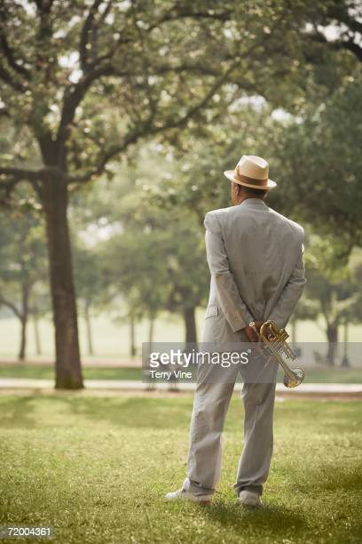 Senior African man standing with trumpet in park