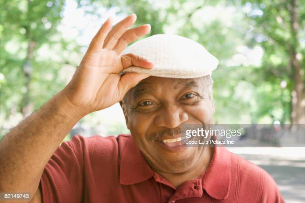 senior african man tipping hat - waving gesture stock photos and pictures