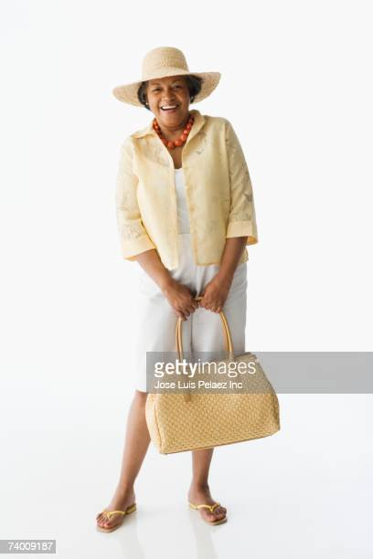 senior african woman holding purse - woman carrying tote bag stock photos and pictures