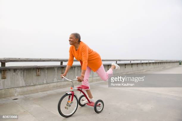 senior african woman playing on tricycle - zorgeloos stockfoto's en -beelden