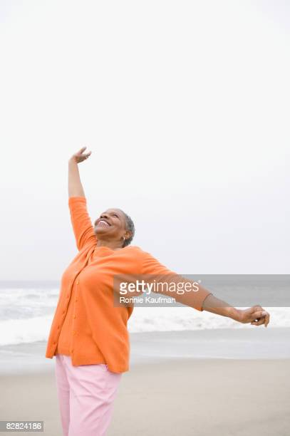 senior african woman stretching on beach - one senior woman only stock pictures, royalty-free photos & images